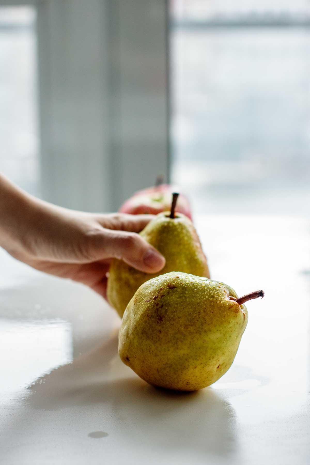 hand grabbing pear