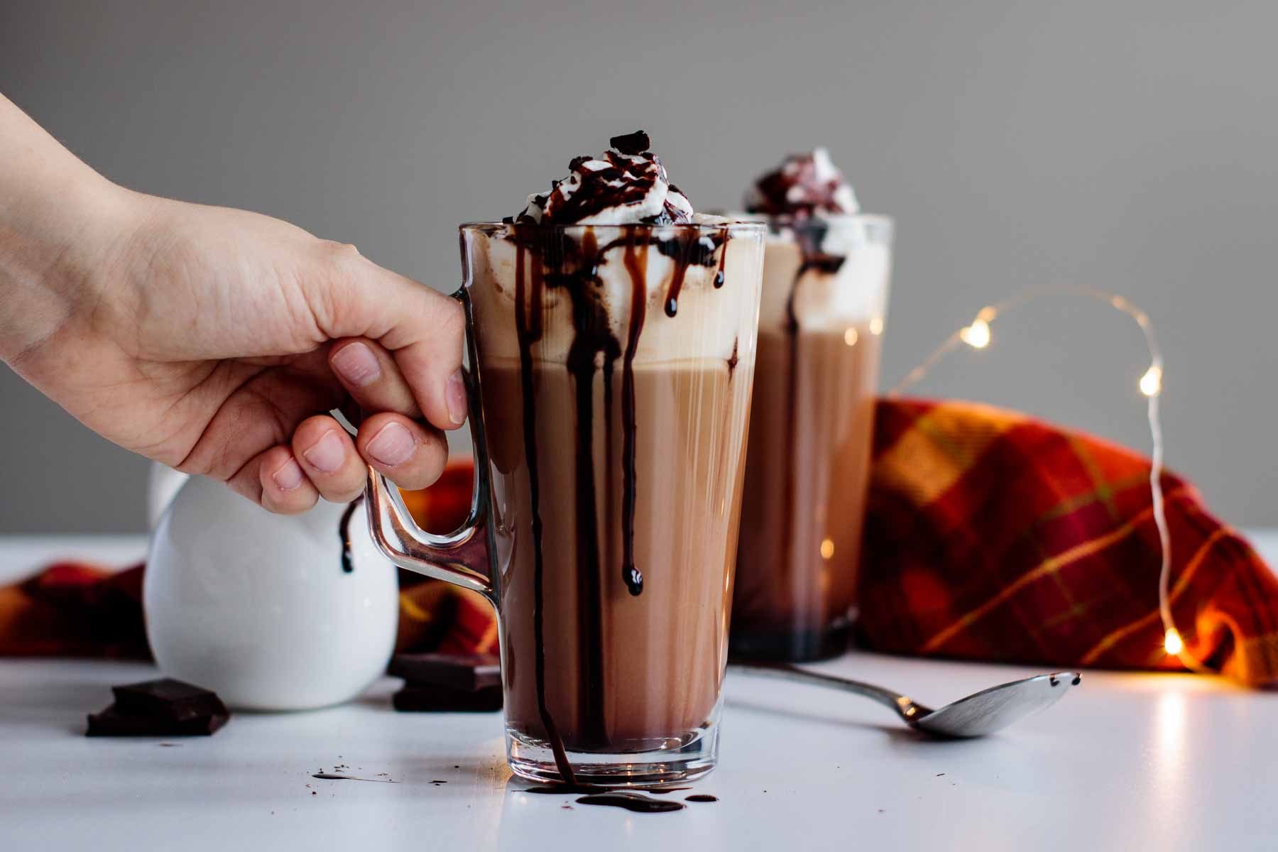 drinks ready, over a white table, with mocha sauce and lights in the background, and a hand ready to grab the closer glass cup