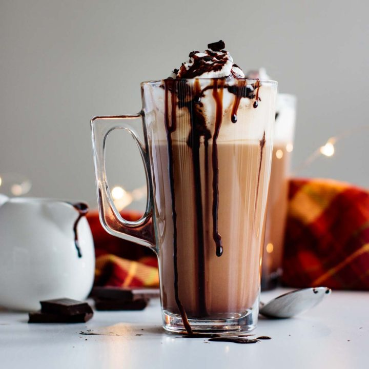 mocha latte ready, with chocolate, mocha sauce and spoon on the background