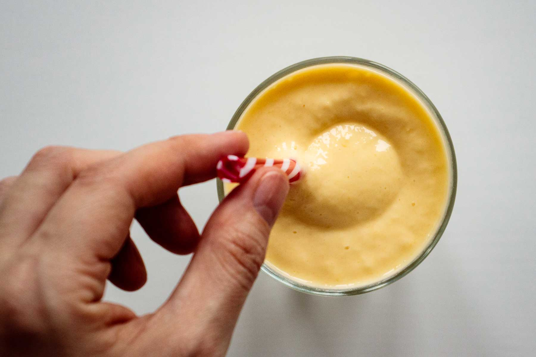 flat lay of smoothie with hand holding a reusable straw