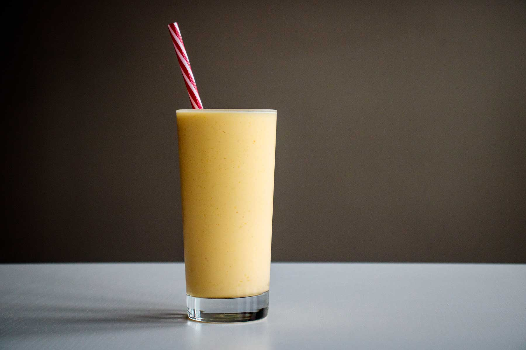 mango smoothie served in a tall glass cup with reusable red straw
