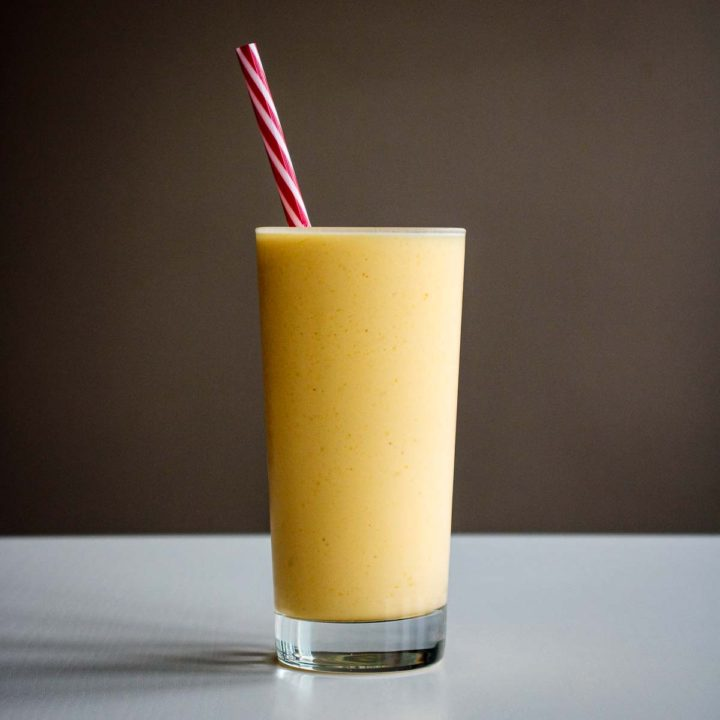 mango smoothie in a tall glass cup with reusable red straw