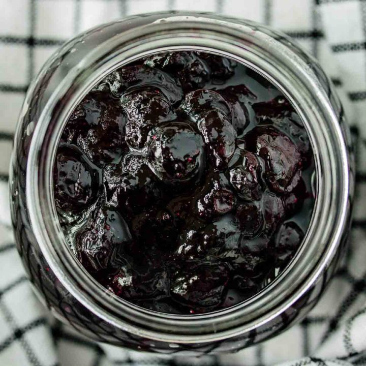 close up of a jar of blueberry compote over a kitchen towel