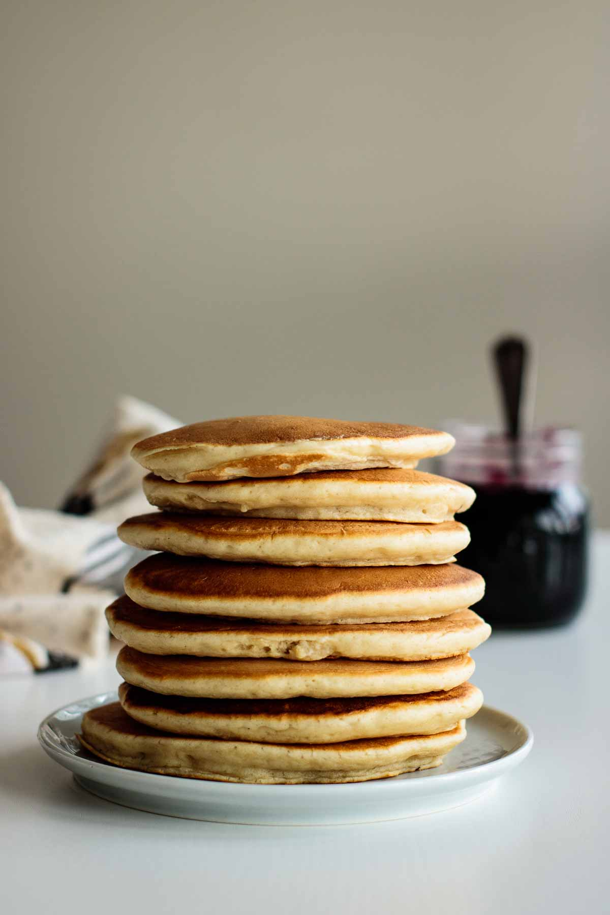 a stack of almond milk pancakes on a plate, with a jar of blueberry compote on the back