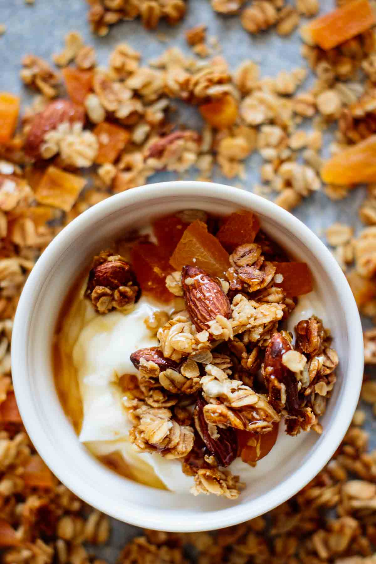 close up on granola bowl, showing granola covered with maple syrup on top of Greek yogurt