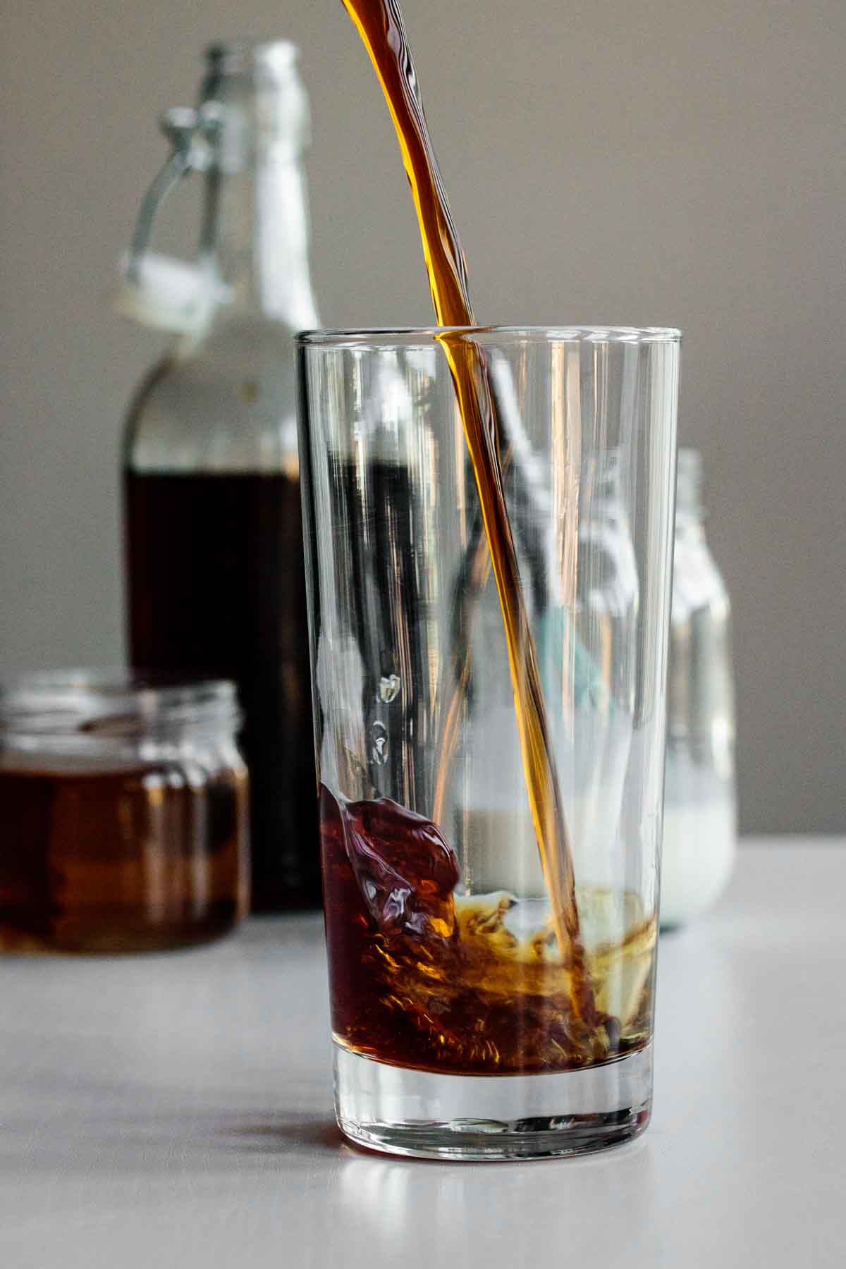 cold brew being poured into tall glass