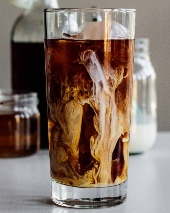 a tall glass of vanilla sweet cream cold brew with cream, syrup and coffee in the back