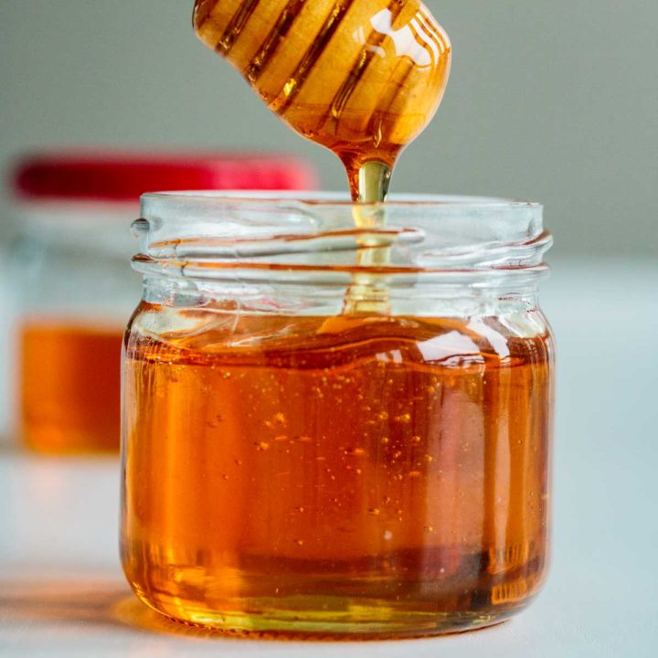 vegan honey dripping off a honey dripper
