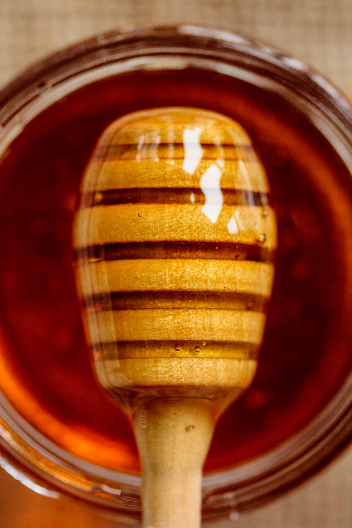 honey dripper close up over a jar filled with this recipe