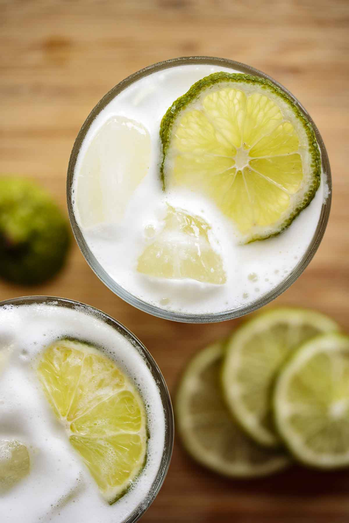 Two glasses of Brazilian limeade with lime slices.