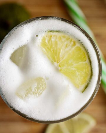 Brazilian lemonade server on a tall glass with lime slice and ice cubes.