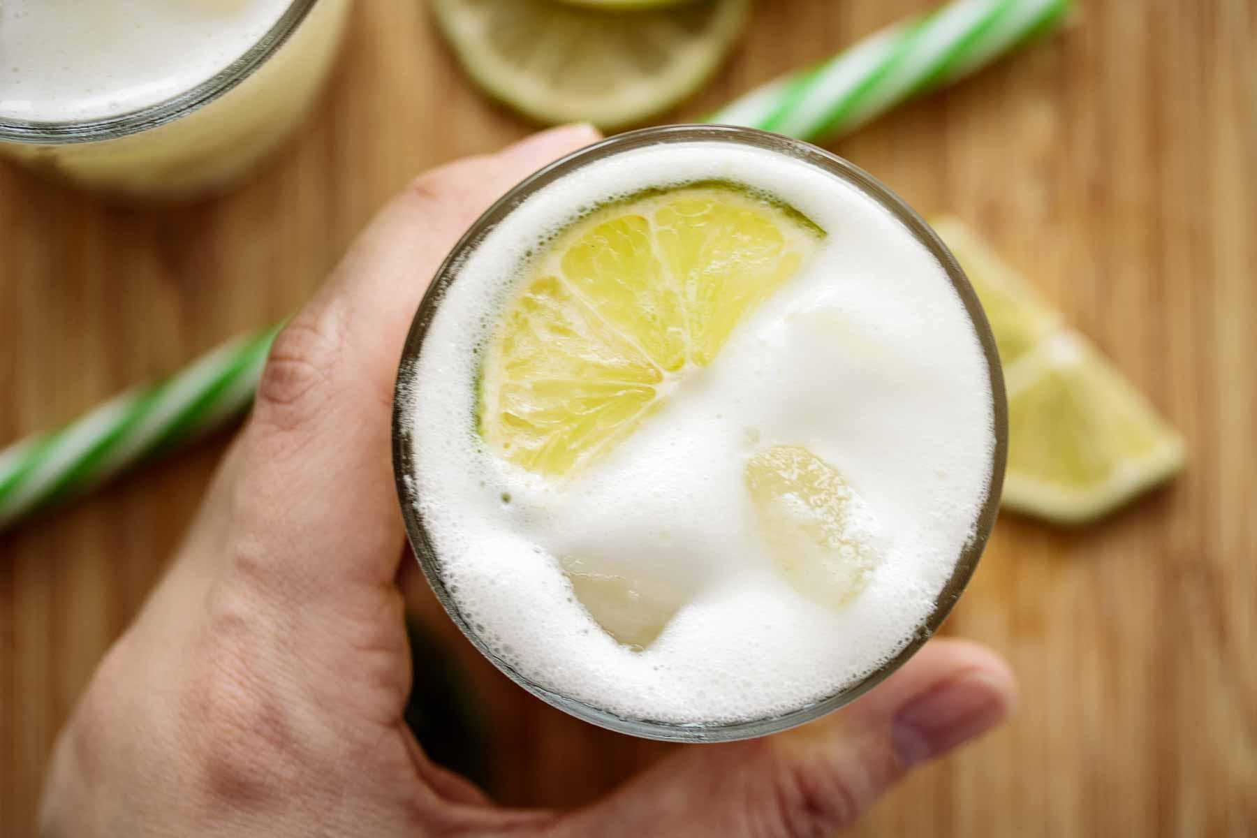 Hand holding a glass of Brazilian lemonade.