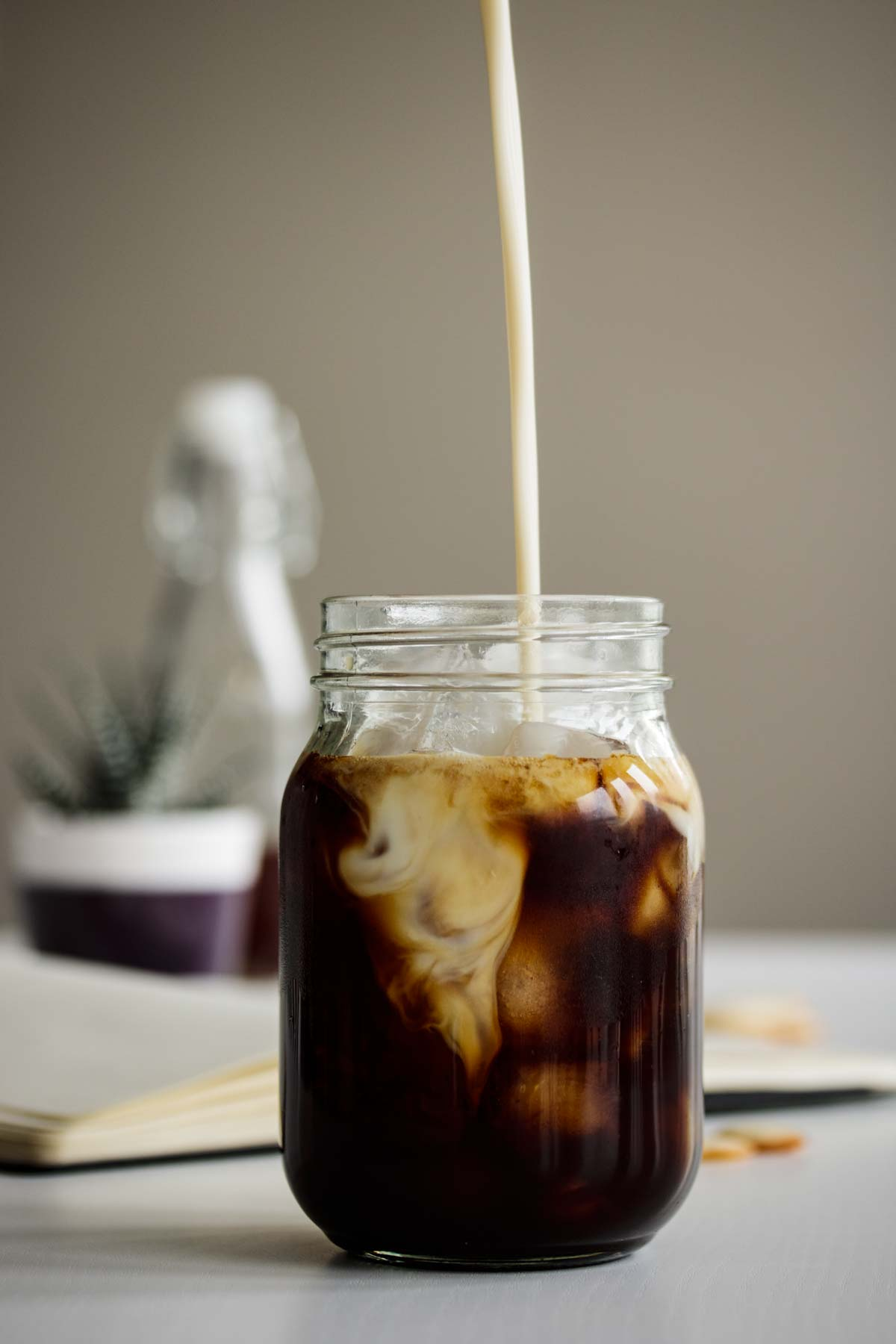 Oat milk pouring into shaken espresso.