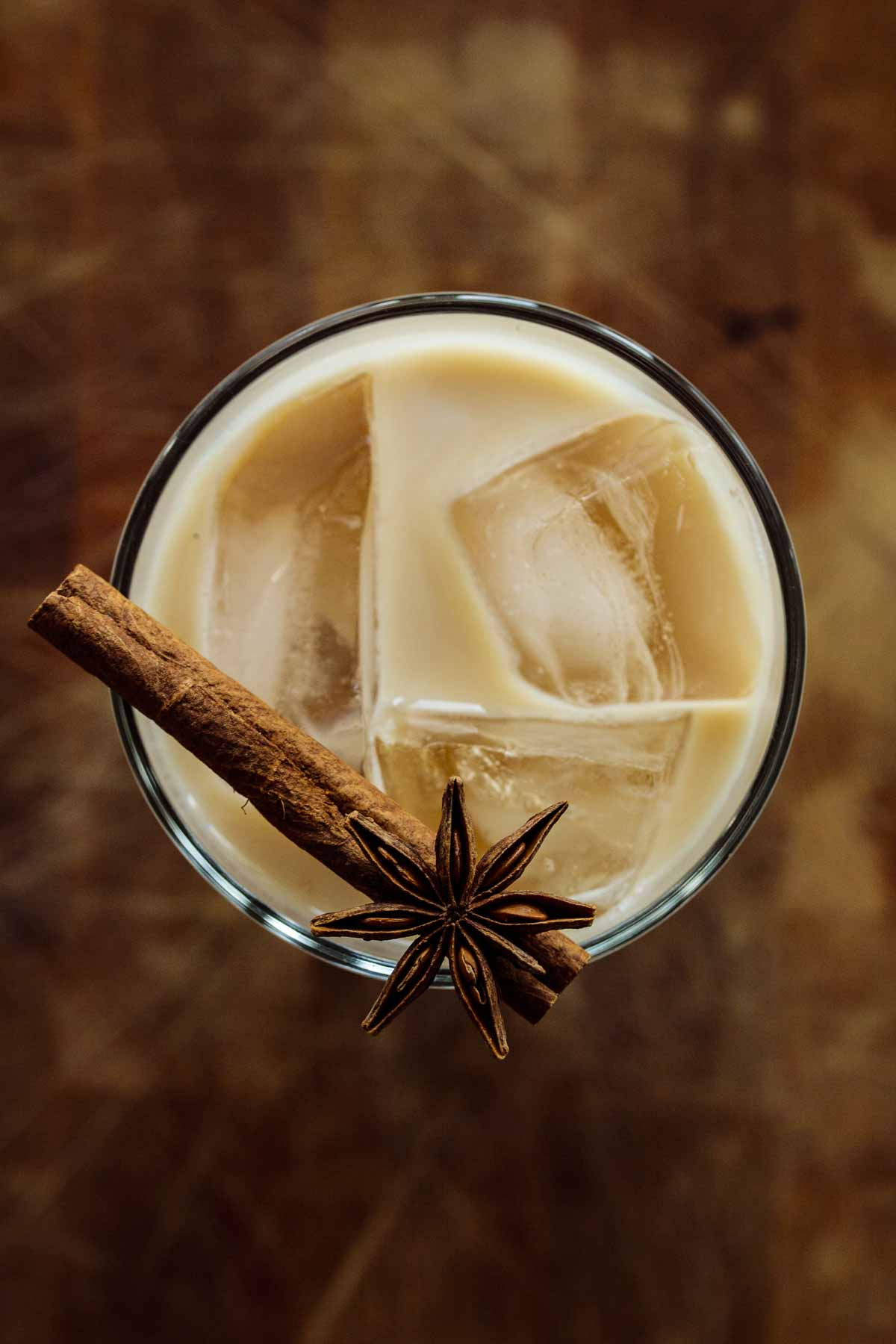 Beverage seen from above, with a cinnamon stick and star anise on the edge of the glass.
