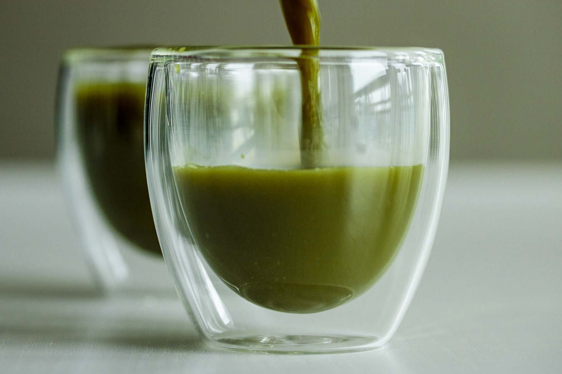 Pouring Macha tea in a transparent glass.