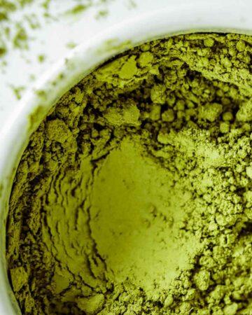 Vibrant green Matcha powder close up, showing its texture.