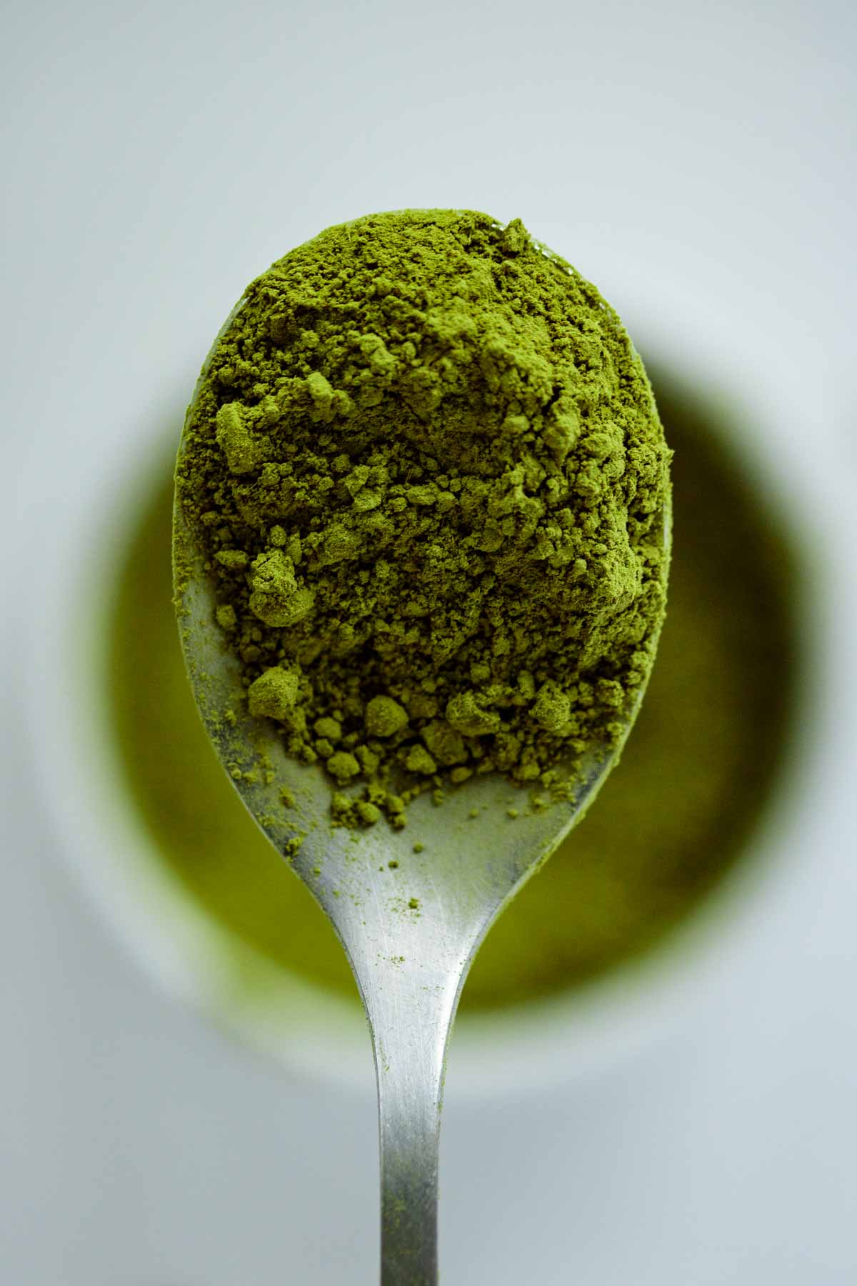 Close up on a spoon filled with vibrant green Matcha powder.