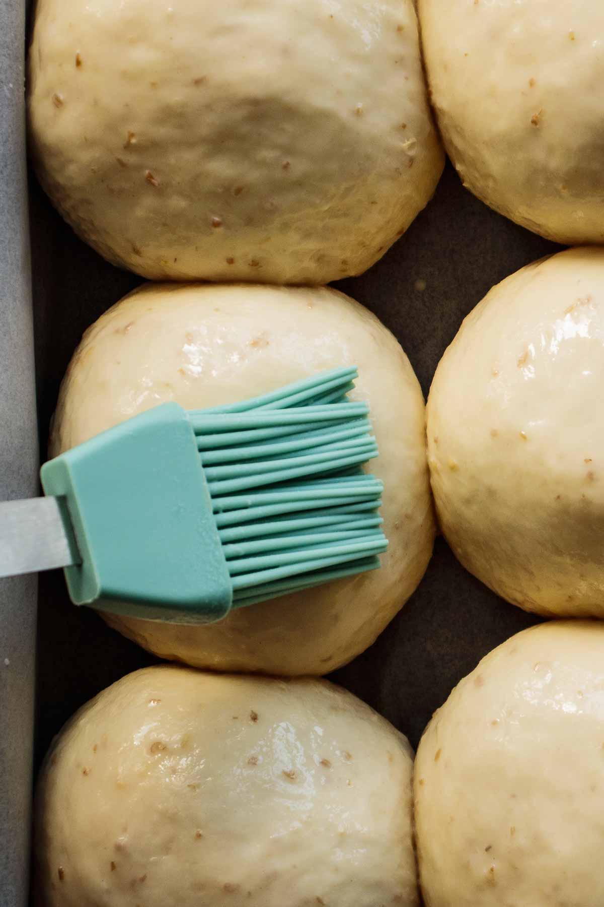 Brush brushing milk and honey wash on top of shaped rolls.