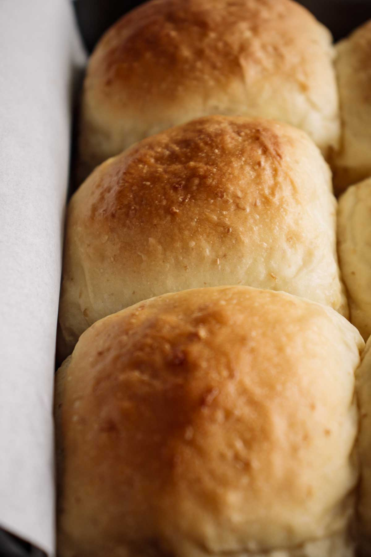 Close up on baked rolls, showing their soft crust.