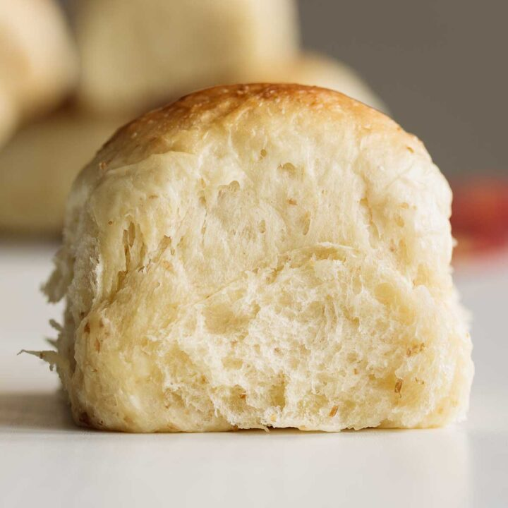 Close up on sourdough dinner roll, showing its soft crumb.