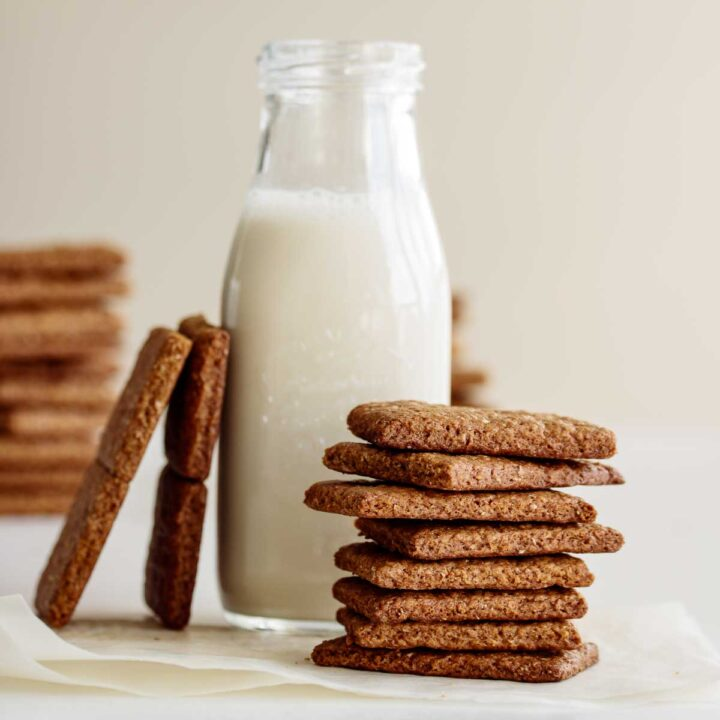 A stack of vegan graham crackers and a bottle of oat milk.