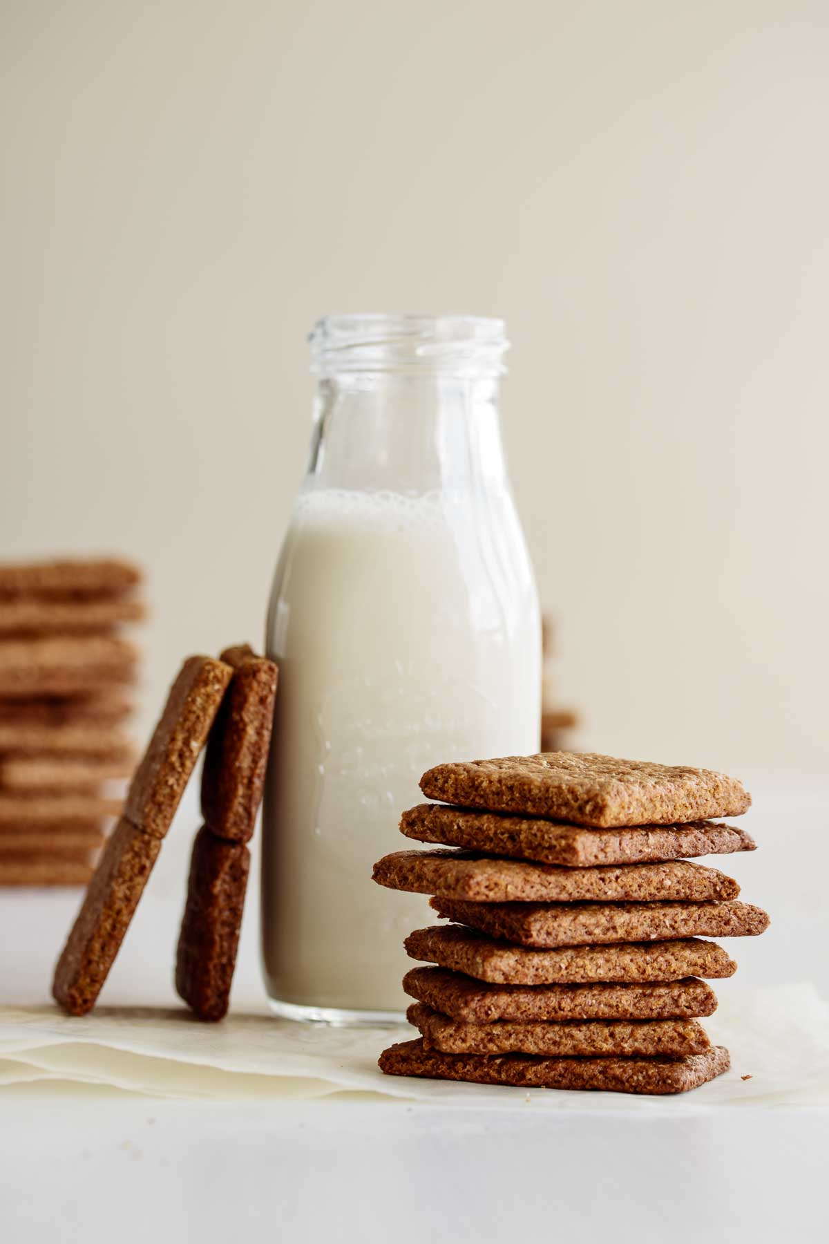 A stack of vegan graham crackers in front of a bottle of oat milk.