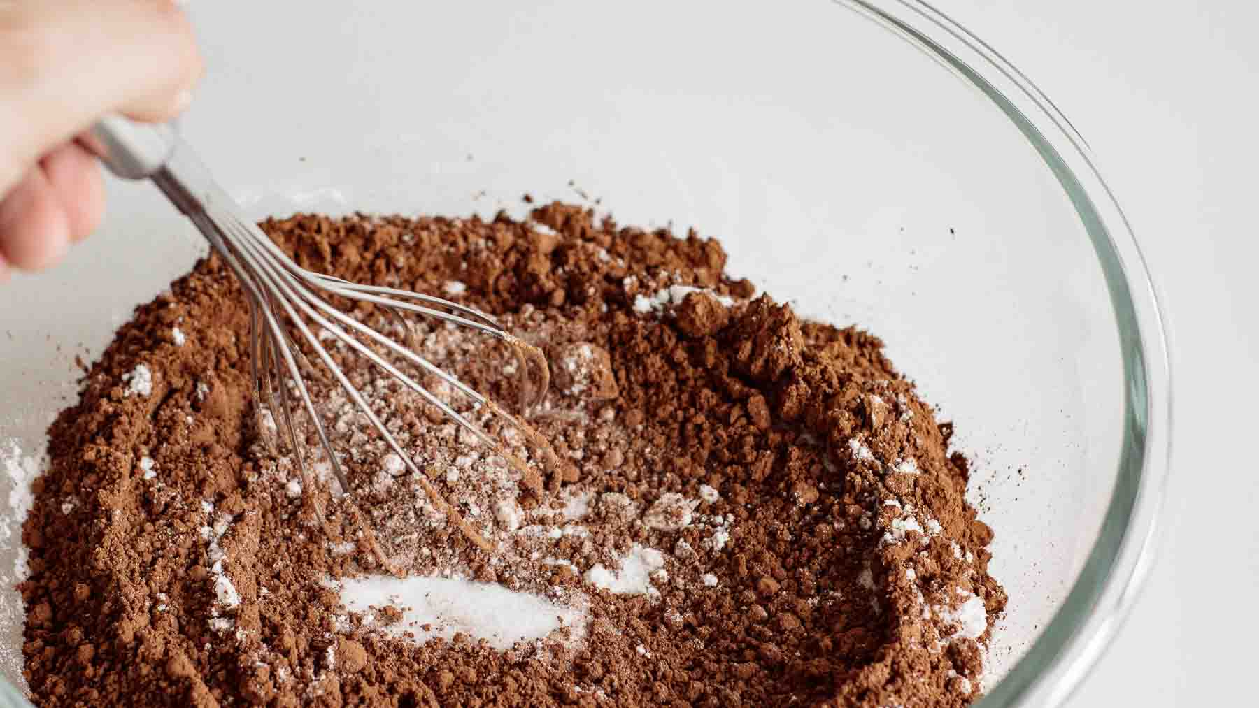 Whisking dry ingredients in a large glass bowl.