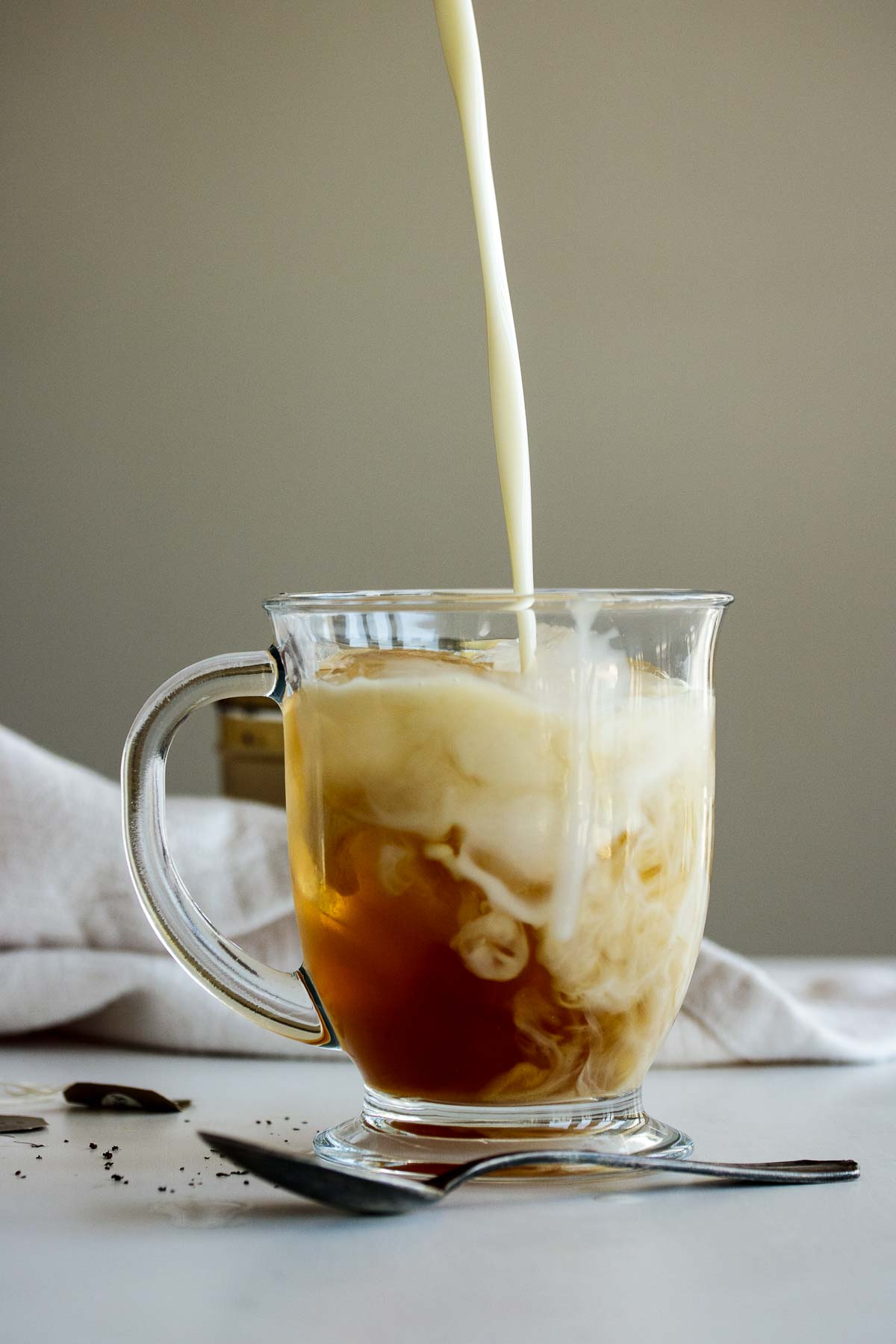 Milk pouring into cold brew earl grey.