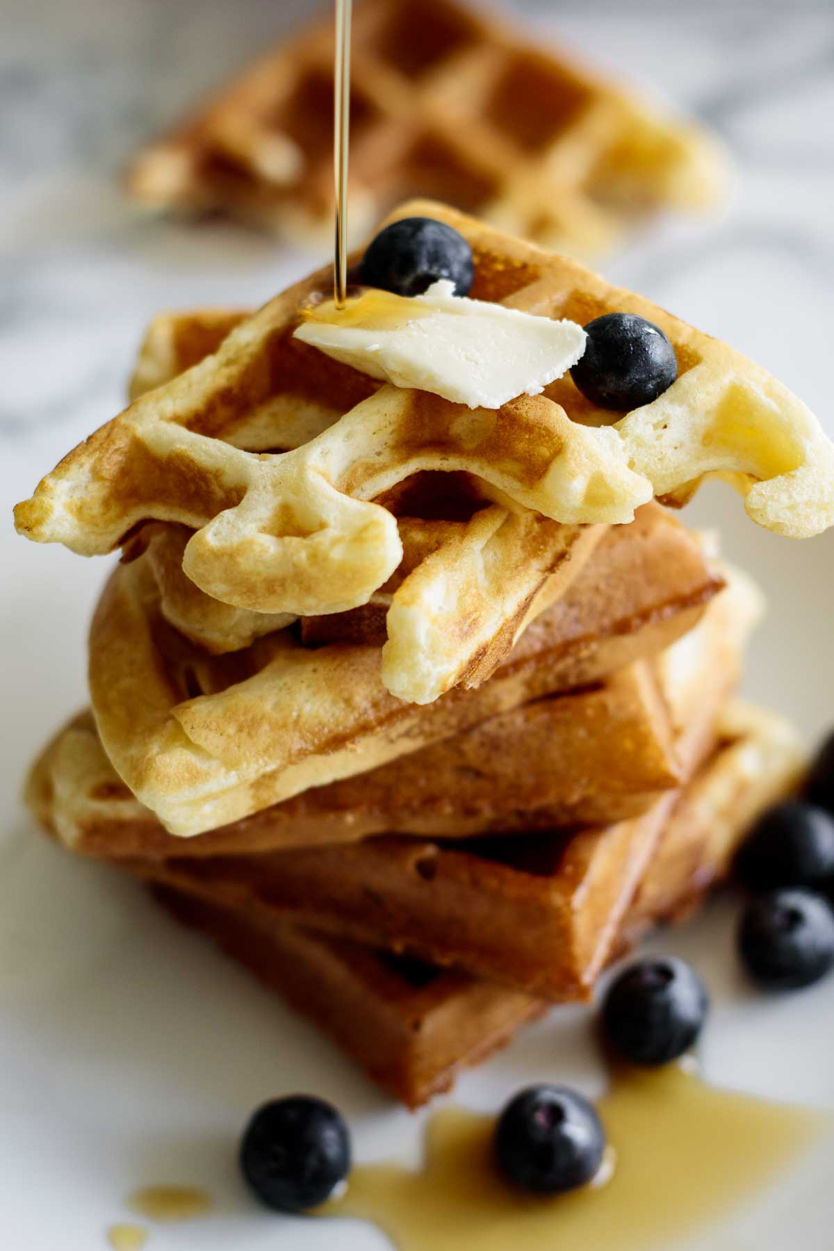 Waffles with berries, maple syrup and butter.