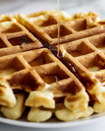 Maple syrup pouring over waffle disk.