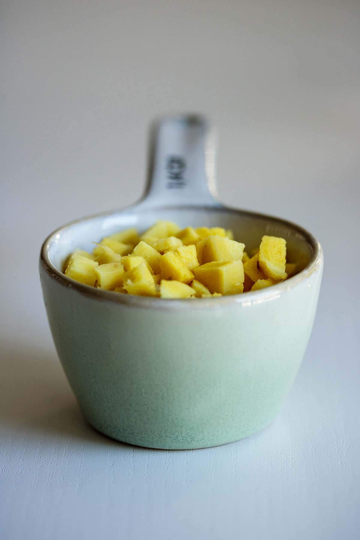 A quarter of a cup filled with cubed ginger.