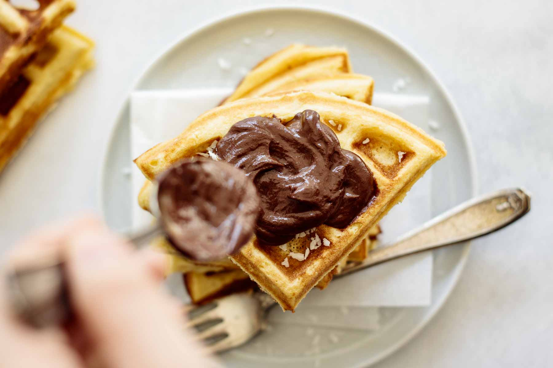 Spoon pouring chocolate ganache over stack of waffles.